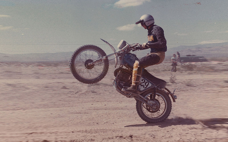 casey folks popping a wheelie on a motorcycle at a best in the desert race