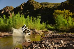 motorcycle racer riding through water at the best in the desert silver state 300