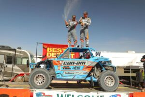 Phil Blurton and co-driver celebrating on podium after winning bitd bluewater desert challenge