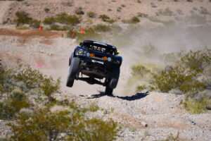 steve olliges driving a trick truck at a best in the desert race